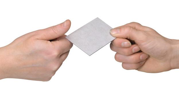 Eine Hand gibt einer anderen eine Visitenkarte.