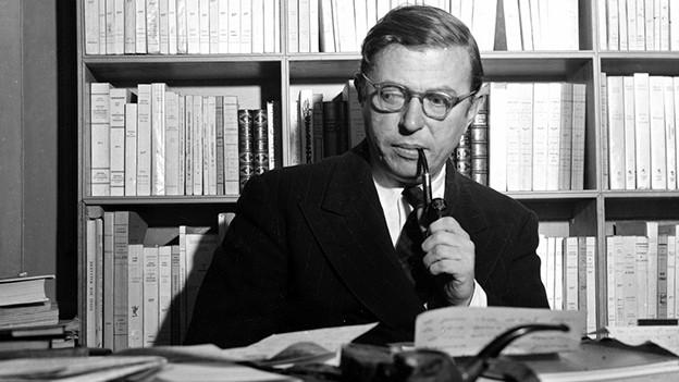 Sartre sitzt mit Pfeife in einem Büro