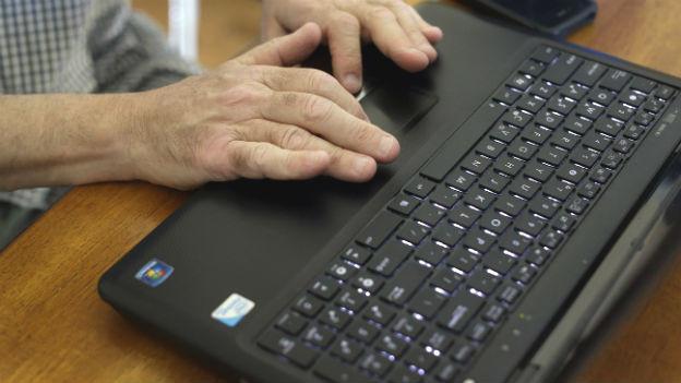 Eine Hand an einem Laptop.