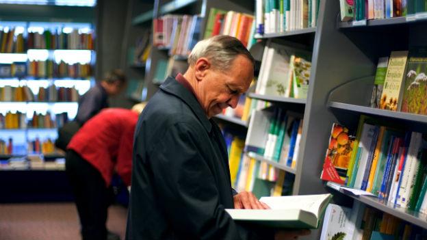 Ein Mann liest ein Buch in einem Buchladen.