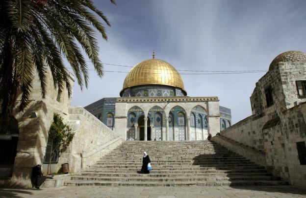 Eine Frau auf der Treppe vor einer Moschee mit goldenem Dach.