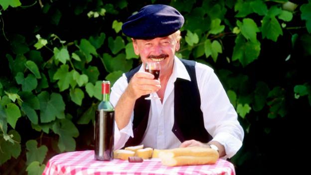 Mann mit Baskenmütze, Schnurrbart, Weinglas und Baguette