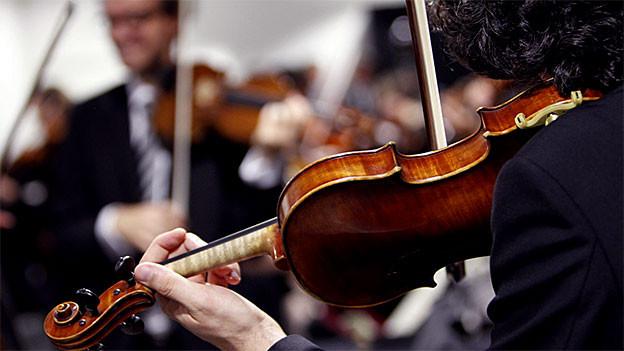 Im Vordergrund ein Geigenspieler von hinten, ihm gegenüber, unscharf, ein anderer Geigenspieler.