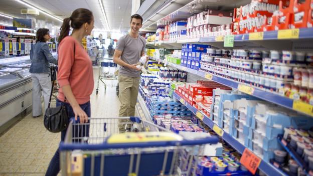 Eine Frau und ein Mann kaufen in einem Lebensmittelgeschäft ein.