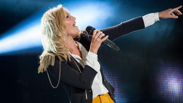 Helene Fischer singt mit glitzerndem Mikrofon.