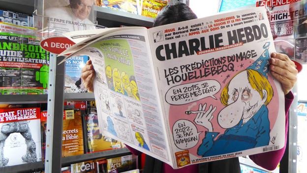 Jemand liest die Zeitung Charlie Hebdo