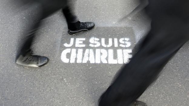 Schuhe auf einer «Je suis Charlie»-Zeichnung.