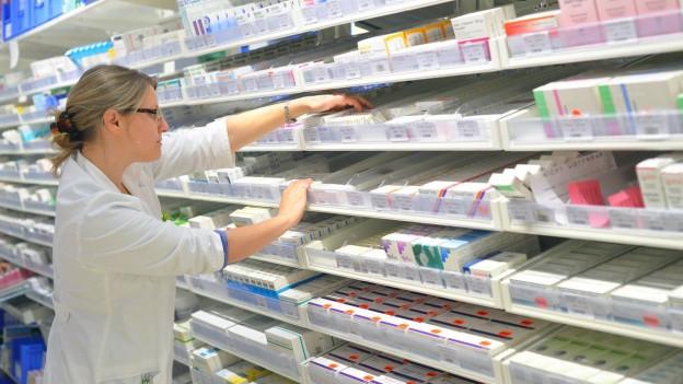 Apothekerin sortiert Medikamente.