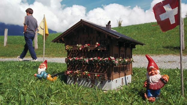 auf einer Wiese steht das Modell eines Chalets mit einer Schweizer Fahne und Gartenzwergen.