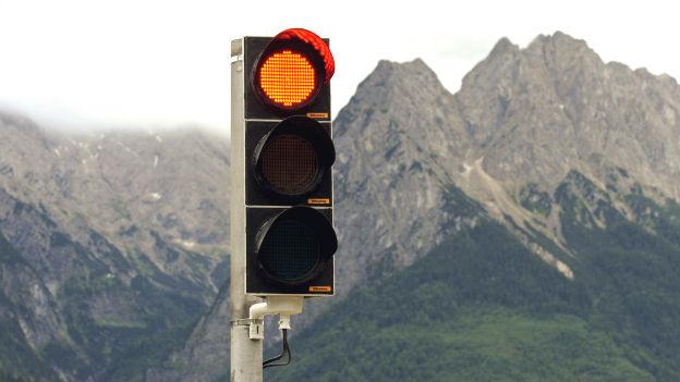 Eine rote Ampel vor einem Berg.