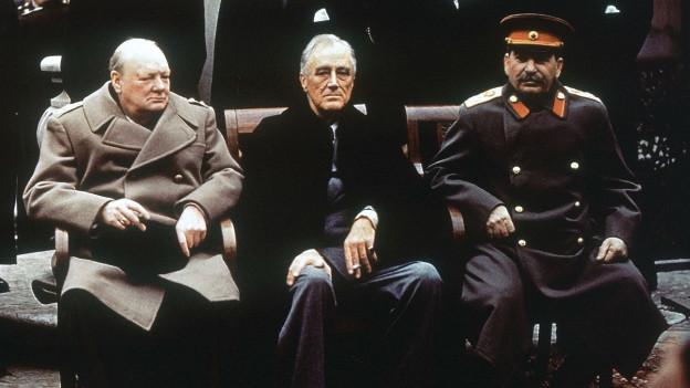 Drei Männer sitzen auf Stühlen und schauen ernst.