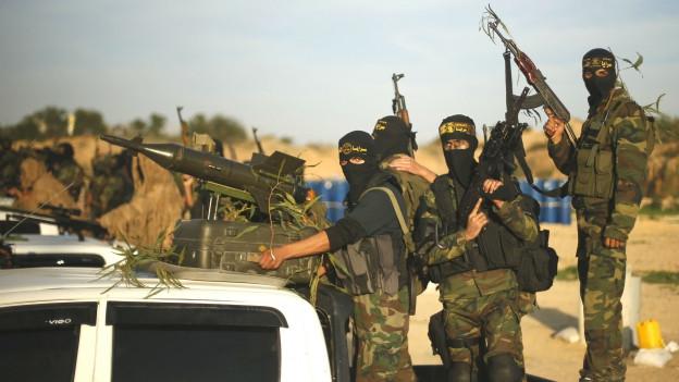 Jihadkämpfer, vermummt vor einem Auto.