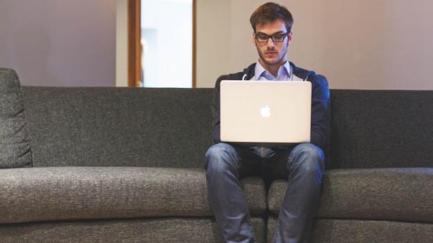 Ein Mann sitzt auf einem Sofa und schaut in ein Laptop.