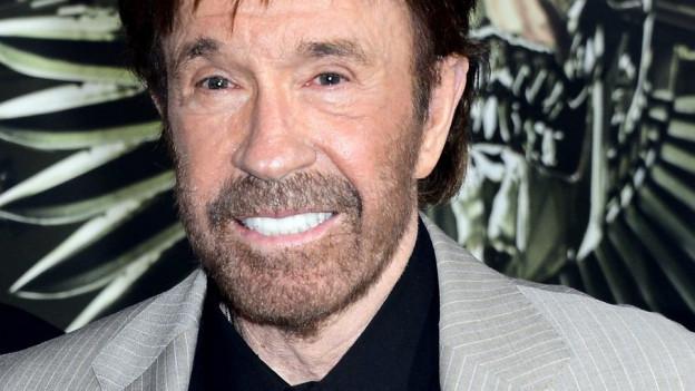 Chuck Norris lächelt. Er hat weisse Zähne und etwas rötliche Haare.