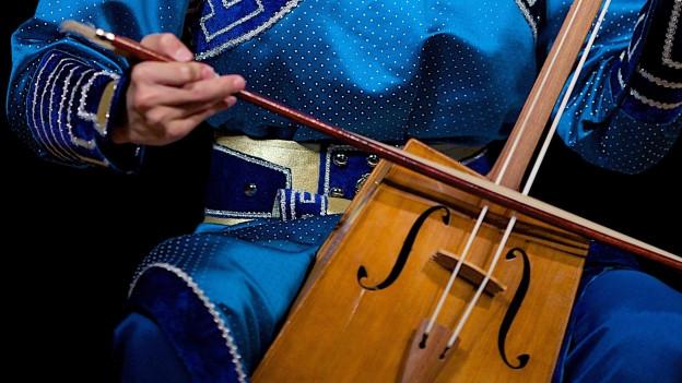 Ein junger Mann aus der Mongolei spielt sein traditionelles Instrument, eine Pferdekopfgeige. Ein Streichinstrument mit einem langen Hals zwei Saiten.
