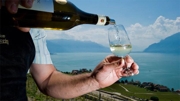 Ein Winzer serviert seinen Wein in Chexbres, hinter ihm der Genfersee.