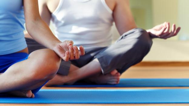 Zwei Menschen sitzten im Schneidersitz auf dem Boden und meditieren.