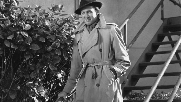 Ein Mann geht eine Treppe hinunter, er trägt einen Trenchcoat und einen Hut.