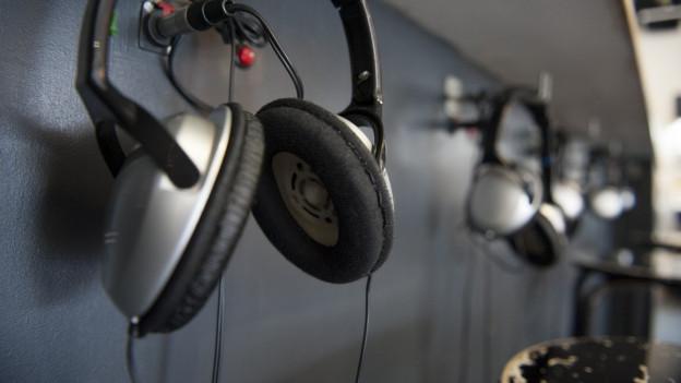 Kopfhörer hängen an einer Wand.
