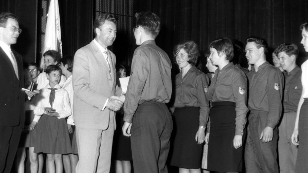 Ein Mann gratuliert einem jungen Mann. Im Hintergrund Jugendliche in FDJ-Uniform.