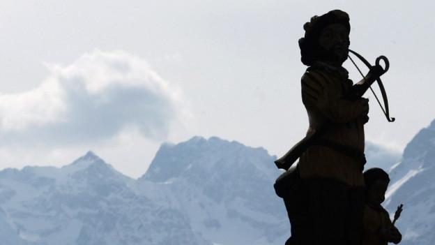 Bergpanorama: Davor Wilhem Tell Statue im Gegenlicht.