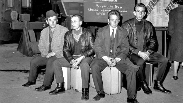 Männer sitzen auf Koffern.