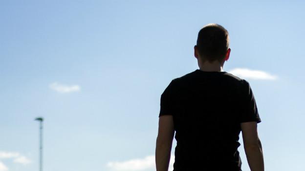 Rückenansicht eines Mannes, der in den Himmel schaut