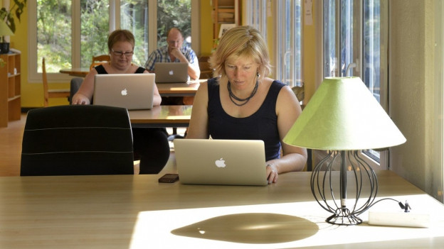 Verschiedene Menschen arbeiten an Tischen.