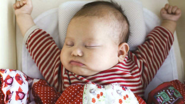 Ein Baby hält die Fäuste hoch. Es hat einen rot-weiss gestreiften Pullover an.