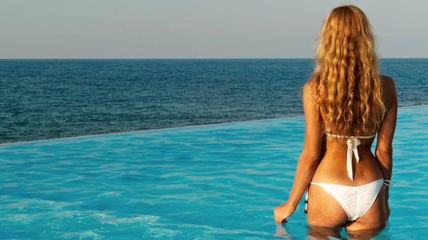 Eine Frau mit einem weissen Bikini. Sie ist in einem Pool und hat den Rücken gegen die Kamera gerichtet.