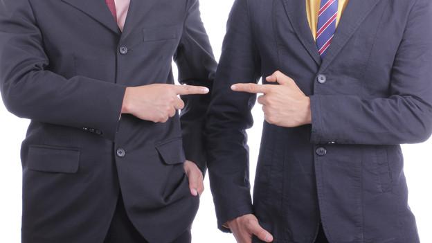Zwei Männer in Anzügen zeigen mit dem Finger aufeinander