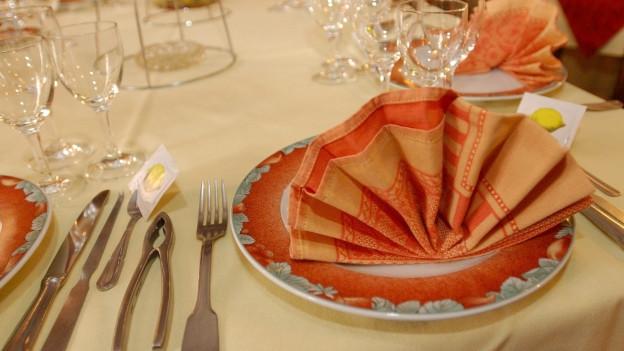 Eine gefältelte orange Serviette auf einem festlich gedeckten Tisch.