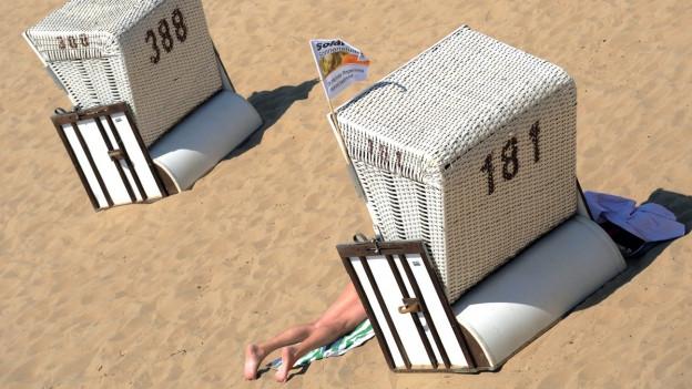 Zwei Strandkörbe von hinten im Sand.