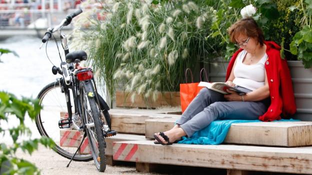 Eine Frau liest an einem Fluss ein Buch. Neben ihr steht ein Fahrrad.