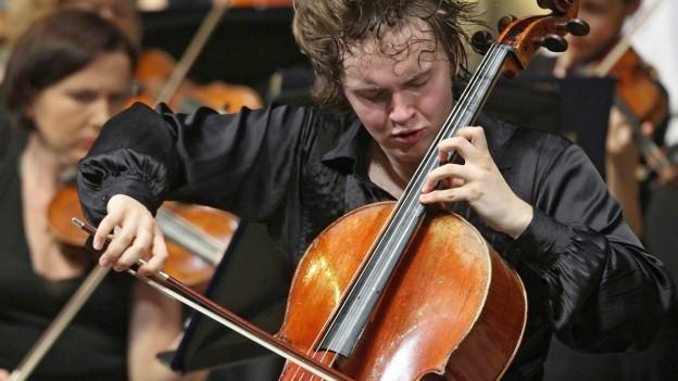 Ein Mann mit schwarzem Hemd spielt mit einem Orchester im Hintergrund hingebungsvoll Cello, seine Haare sind verschwitzt.