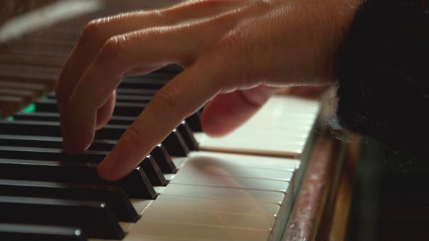 Eine Hand an einem Klavier.