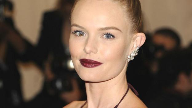 Kate Bosworth in einem dunkelroten Federkleid.