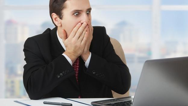 Ein Mann schaut mit weit aufgerissenen Augen und Händen vor dem Mund auf einen Computerbildschirm.