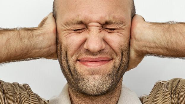 Ein Mann hält sich die Ohren zu.