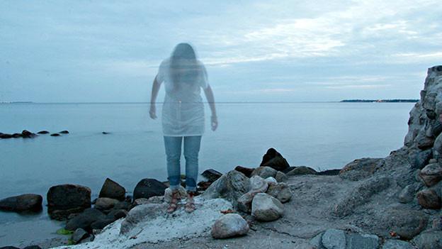 Halbdurchsichtige Frau steht am Meer.