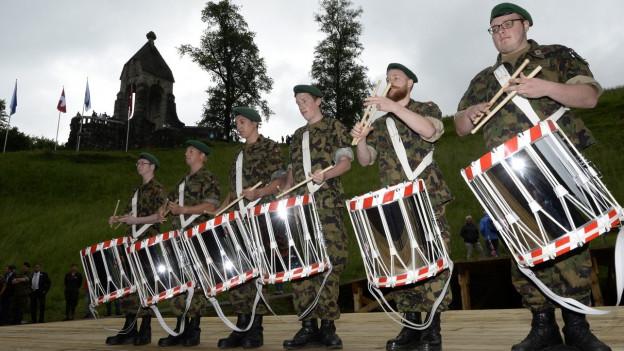 Trommler in Militäruniform stehen in einer Reihe.