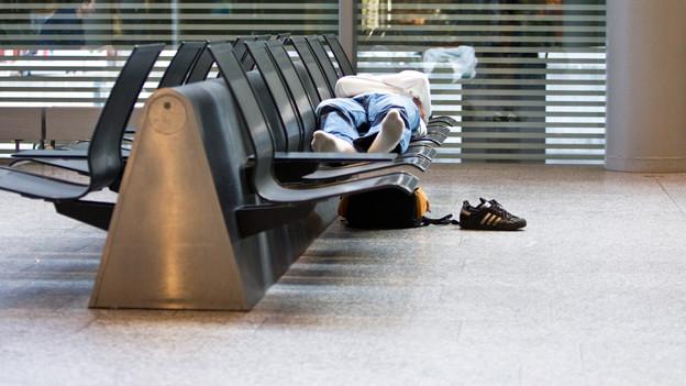 Ein Mann schläft in einer Flughafenhalle.