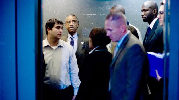 Ein paar Männer stehen zusammen in einem Lift.