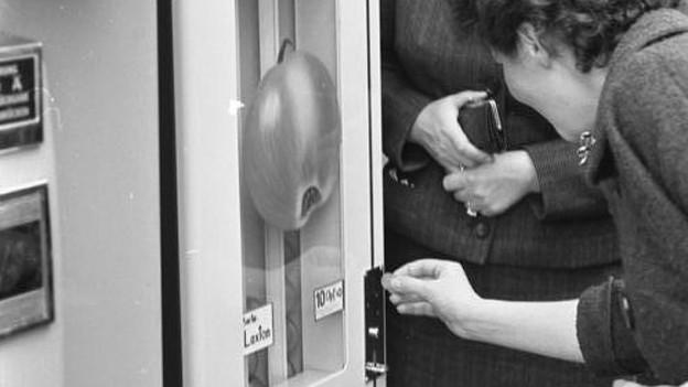 Zwei Frauen werfen Kleingeld in einen Automaten, auf dem ein grosser Apfel klebt.
