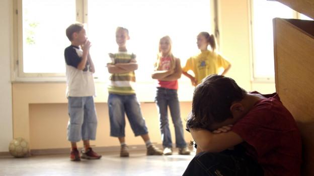 Ein Junge sitzt am Boden mit dem Kopf auf dem Knien. Dahinter steht eine Schülergruppe..
