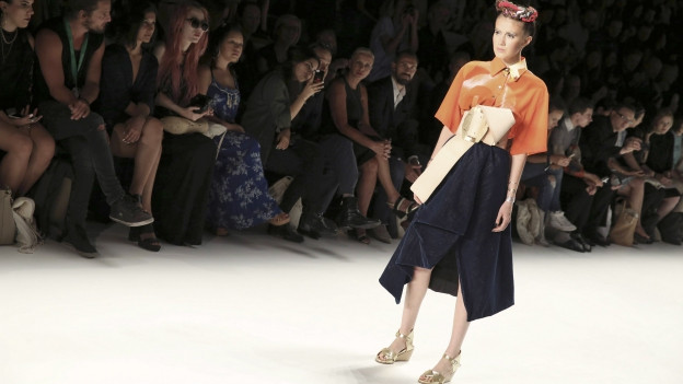 Eine Frau mit dunklem Rock, orangenem Top und überdimensional breitem Gürtel auf dem Laufsteg.