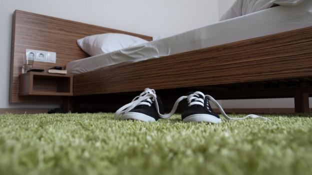 Ein Bett, ein grüner Teppich und Schuhe darauf.