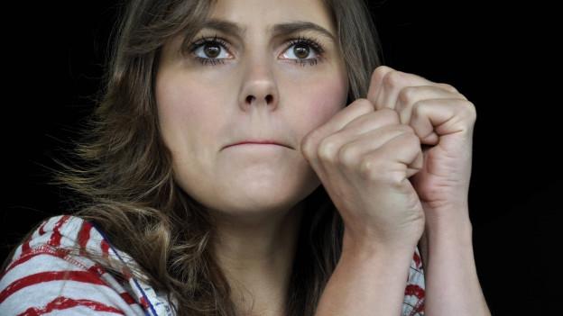 Eine Frau hat beide Daumen gedrückt, ihre Lippen sind zusammengepresst.