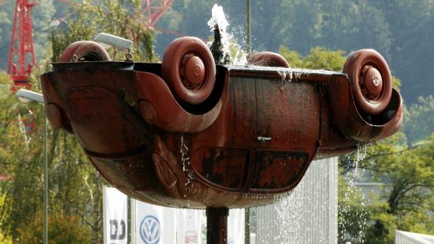Ein rostroter Volkswagen, der auf dem Kopf steht und als Springbrunnen dient.