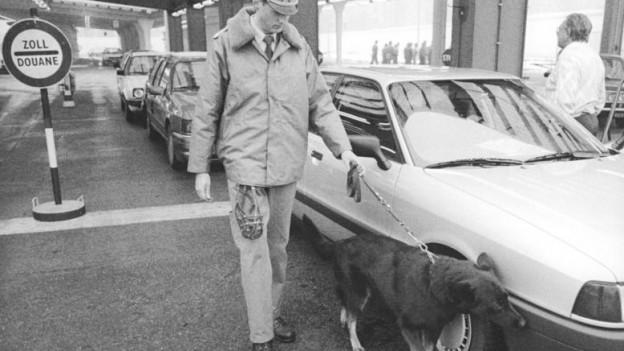 Schwarz-Weiss-Foto: Ein Zollbeamter kontrolliert ein Auto mit einem Hund.